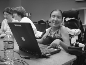 Photo of DO-IT Scholar in wheelchair smiling at the camera while she uses the touch-pad on her laptop.