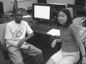 Image of two DO-IT Scholars looking away from their shared computer screen to pose for a picture