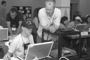 Photo of Members of the program staff help DO-IT Scholars who are working on projects on their laptops.