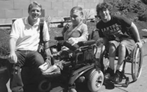 Two DO-IT Scholars in wheelchairs pose for a picture with Staff member Scott