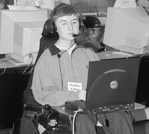 Photo of DO-IT Scholar in wheelchair typing on a computer in his lap.