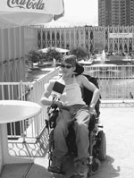Image of a DO-IT Scholar wearing sunglasses poses in her wheelchair on a patio.