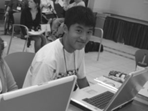 Photo of DO-IT Scholar looks up from his laptop to smile at the camera.