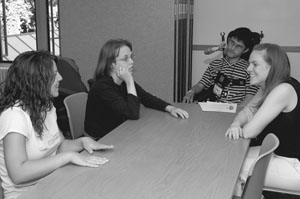 Image of Scholars and Mentors gathering around a conference table for a mock interview.