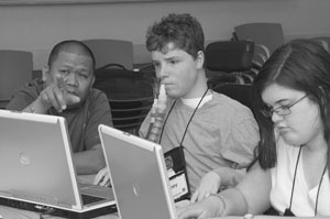 Image of three Scholars gather around two laptops, brainstorming.