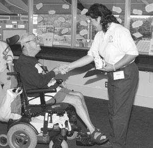 Image of a Scholar in a wheelchair receiving an award.