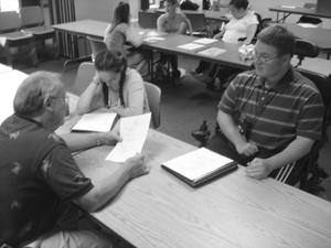 Photo of two students are interviewed by an adult and interviews are going on in the background.