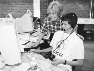 Photo of Sheryl Burgstahler helps a Scholar at the computer in the computer lab.