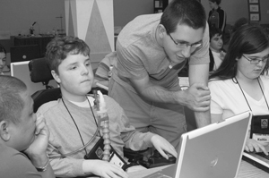 Photo of DO-IT Mentor assisting a DO-IT Scholar on the computer.