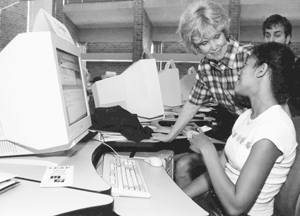 Photo of DO-IT Scholar consulting DO-IT director Sheryl Burgstahler on a computer issue while in the computer lab with other DO-IT Scholars.