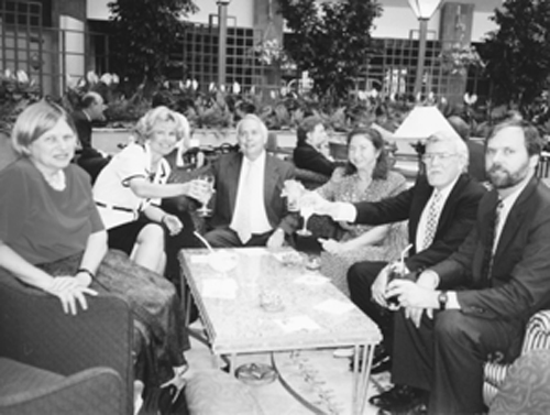 Photo of Six adults sit around a table and raise their glasses for a celebration toast.