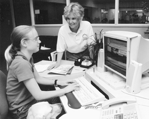 Photo of DO-IT Director Sheryl Burgstahler advises a DO-IT Ambassador while she works on her computer in an office setting.