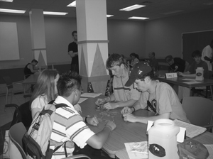 Photo of Four students working in a group to solve a problem sit around a table in a classroom.
