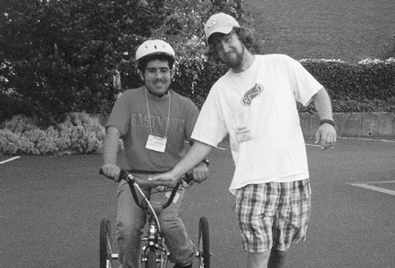 Picture of DO-IT Phase II Scholar Israel on a bike with DO-IT staff member James holding the handlebars.