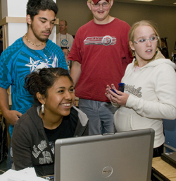 Photo of several students gather around a laptop