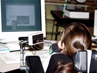 Photo of a student in a wheelchair using adaptive techonlogy to control a laptop.