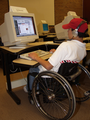 Photo of student in a wheelchair working at a computer workstation.