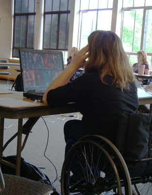 Photo of female student in a wheelchair at a computer