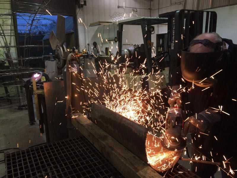Artist using angle grinder on metal piece