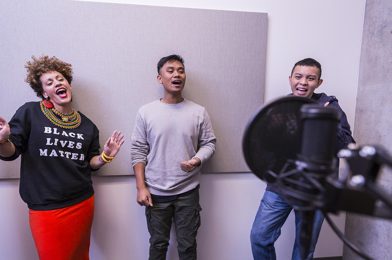 Assistant Director and lead producer Aina Braxton, '12, composer Bryce Villanueva, '16, and test-team member JC Ignacio share a laugh in the recording room