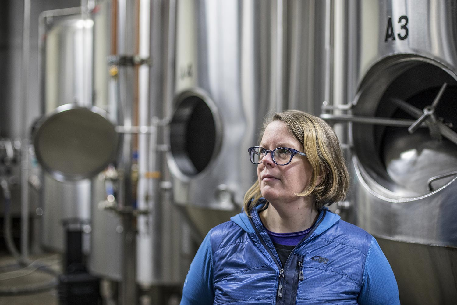 Lisa Ulrich standing by brewing vats