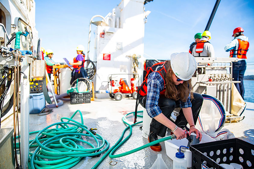 Graduate student Amy Wyeth rinses off equipment before it is reused on a zooplankton-catching device known as a multinet.